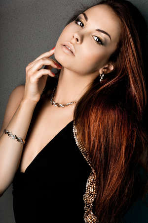elegant fashionable woman with golden jewelry photo