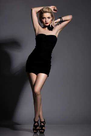 schöne modische Frau im schwarzen Kleid Standard-Bild