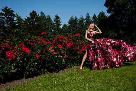 beautiful fashionable woman in a garden with roses photo