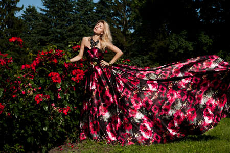 beautiful fashionable woman in a garden with roses Stock Photo - 15574689