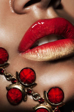 female lips with golden jewelry photo