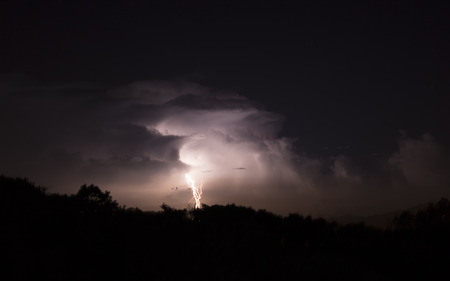 Beautiful lighting bolt and lit up clouds in the night sky