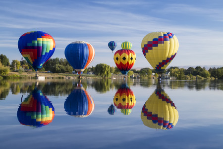 Hot Air Balloons touching down on the water with reflection