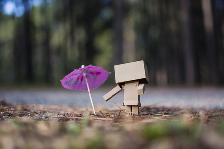 Robot toy and umbrella on the road with the pine forest in the background