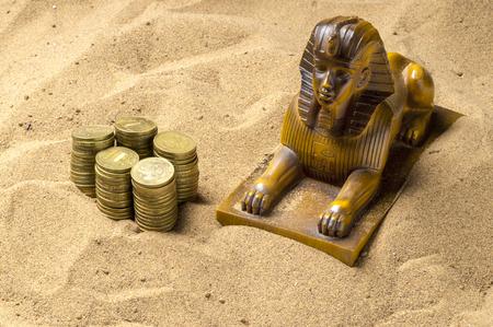 esfinge: Esfinge y las monedas en la arena Foto de archivo