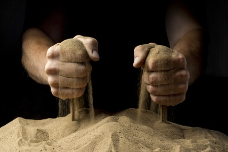 strewed: sand fist on a black background Stock Photo