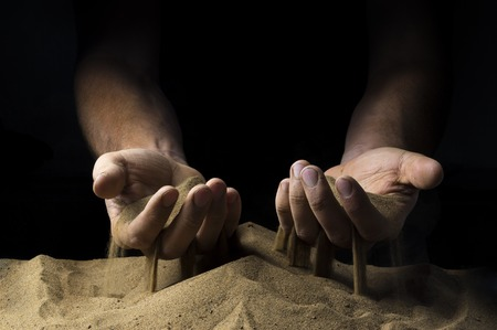 strewed: pours sand from his hands on a black background Stock Photo