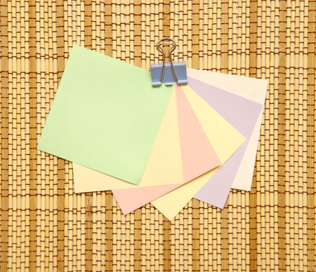 Colourful Notes with paper clip on straw rug photo