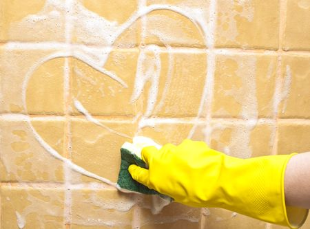 scrubbing up: hand in yellow rubber glove draws heart Stock Photo