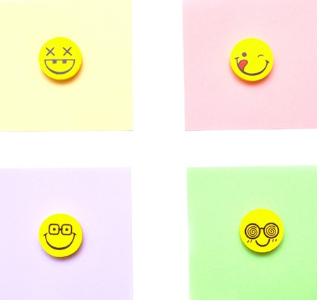 four of yellow smiley on a color paper background photo