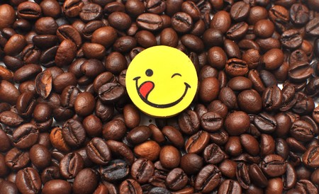 yellow button is a happy face on the background of the coffee bean photo