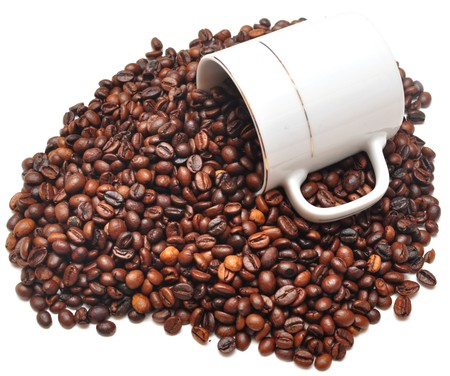some coffee beans falling from a coffee cup on white background photo