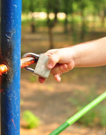 touched: childs hand touched the closed lock on the lattice
