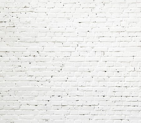 white brick wall: A white roughly textured brick wall painted with white paint