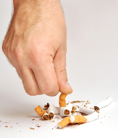 cease: hand man crushes last cigarette. stop smoking