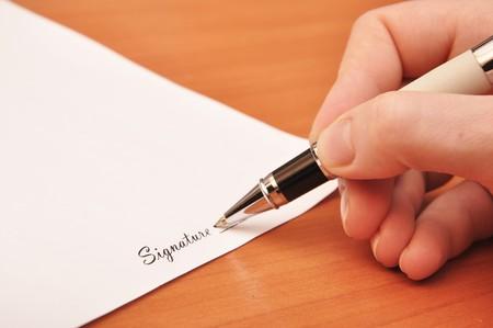 signing: mano alzato con penna firma un contratto