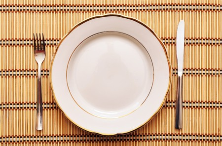 cooking ware: empty plate with fork knife on table