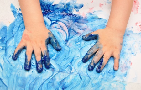 fingerpaint: child hands painted in blue paint ready for hand prints