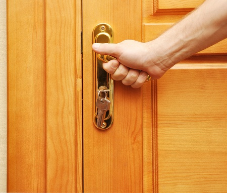 hand on a handle wooden door to open or close it   photo