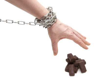 sinful: a womans hand reaching for a chocolate candy