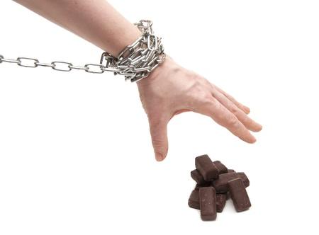 abstinence: mano di una donna raggiunge una caramella al cioccolato