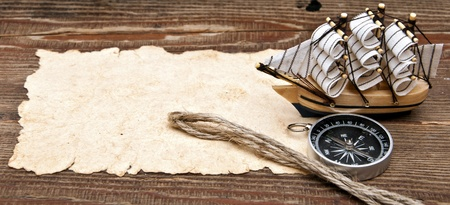 old paper, compass, rope and model classic boat on wood background Stock Photo - 8572633