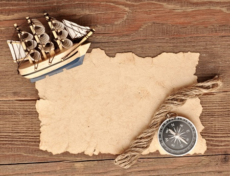 ancient ships: old paper, compass, rope and model classic boat on wood background