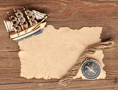 oude papier, kompas, touw en model klassieke boot op hout achtergrond