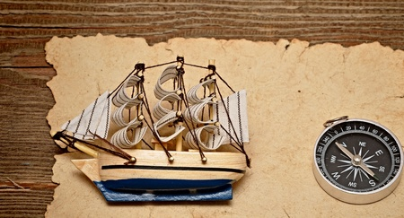 yellow boats: old paper, compass, and model classic boat on wood background