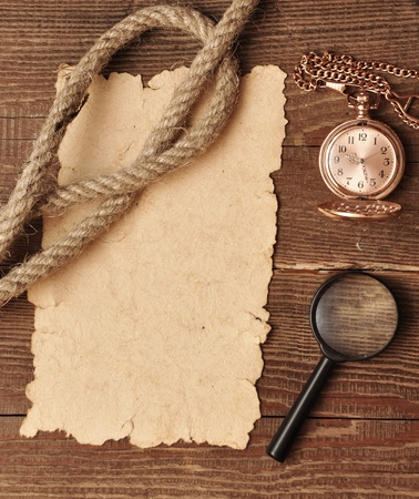 old paper with pocket watch and magnifying glass on wood background photo