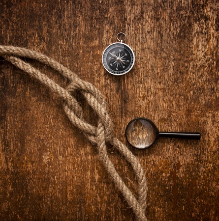 compass, magnifying glass and rope on grunge background photo