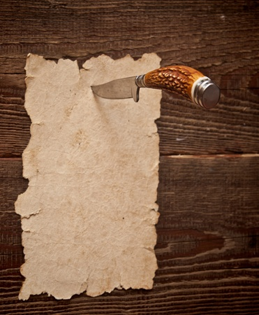 Old paper pinned to a wooden wall with a knife photo