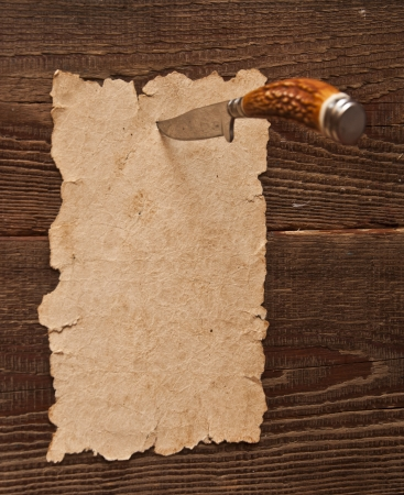 Old paper pinned to a wooden wall with a knife Stock Photo - 8787876