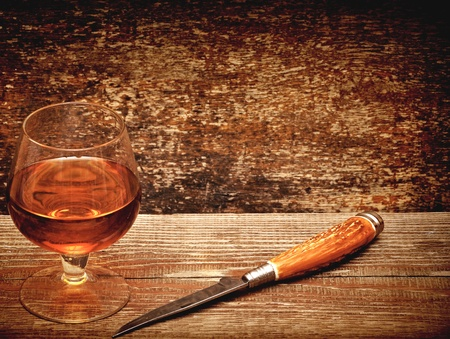 drunks: knife and cognac on wood background