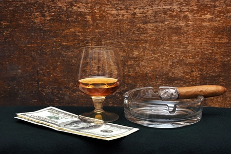 Smoking cigar in an ashtray and glass cognac on green felt photo