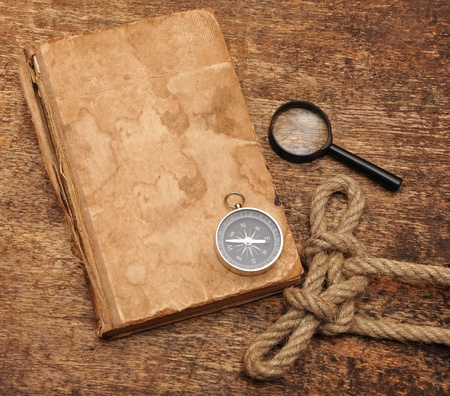 Old book, compass and magnifying glass on wood background photo