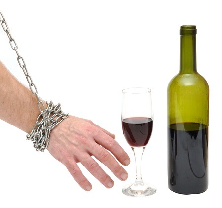 drunkenness: chained hand reaches for the bottle - stop alcoholism concept