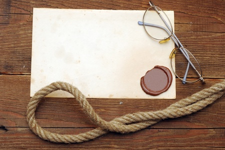 Old paper with a wax seal on a wood background photo