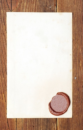 credence: Old paper with a wax seal on a wood background