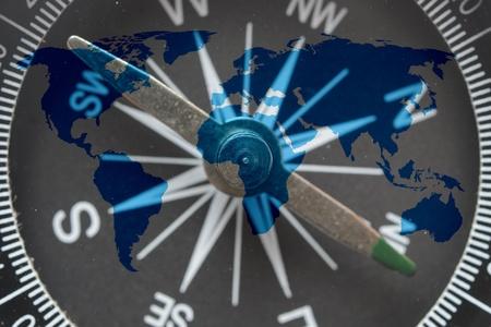 world map on glass compass photo