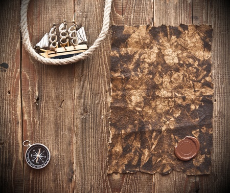 old paper, rope and model classic boat on wood background photo