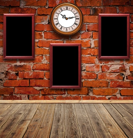 empty photo frames and watch against an brick wall in old room  photo