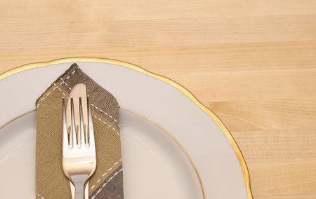 Knife and fork with white plate on wooden table photo