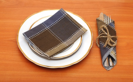 knife and fork in textile napkin on wooden table photo