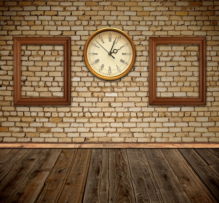 against the clock: empty photo frames and wall clock against an wall in old room