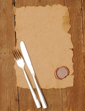knife and fork on old paper. space for the text photo