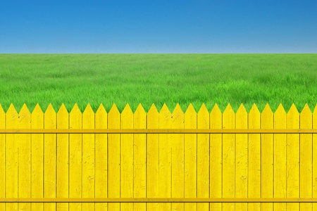 yellow fence with grass on clear blue sky