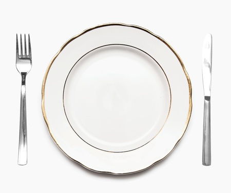 plate setting: Knife, white plate and fork on a white background