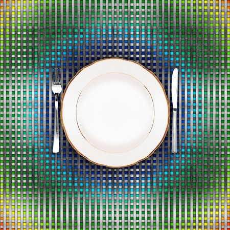 Knife, plate and fork on color grid background photo