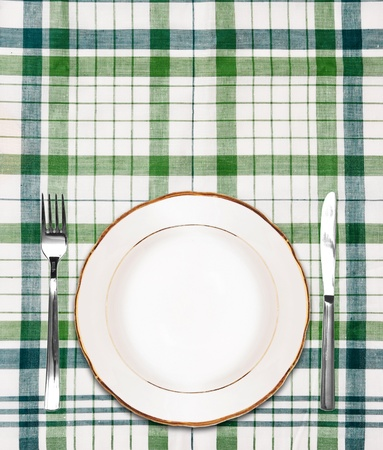 white plate on green checkered tablecloth with knife and fork photo